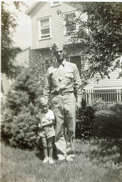 Man in military dress standing in front of house with young boy